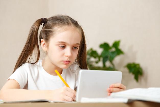 Mała dziewczynka odrabiania lekcji w domu przy stole. dziecko uczy się w domu. dziewczyna o jasnych włosach wykonuje zadanie online za pomocą laptopa i tabletu.