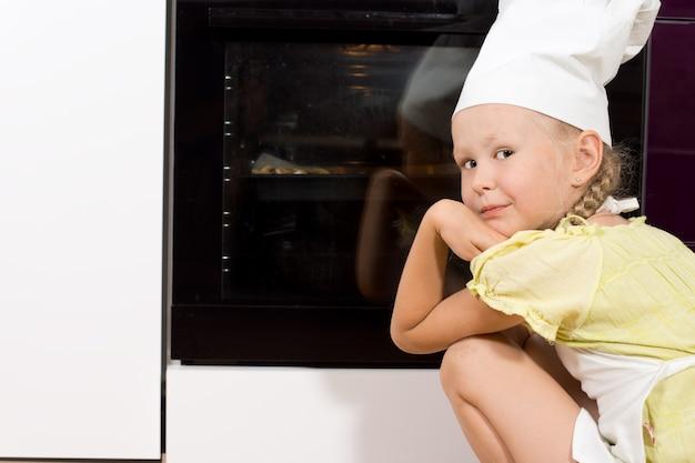 Mała dziewczynka ogląda swojego domowego kucharza pizzy