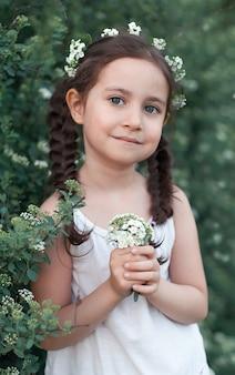 Mała dziewczynka ogrodnik w krzakach białych kwiatów.dziecko opiekuje się roślinami. dzieciak z koszem kwiatów. dziewczyna trzyma w rękach białe kwiaty.