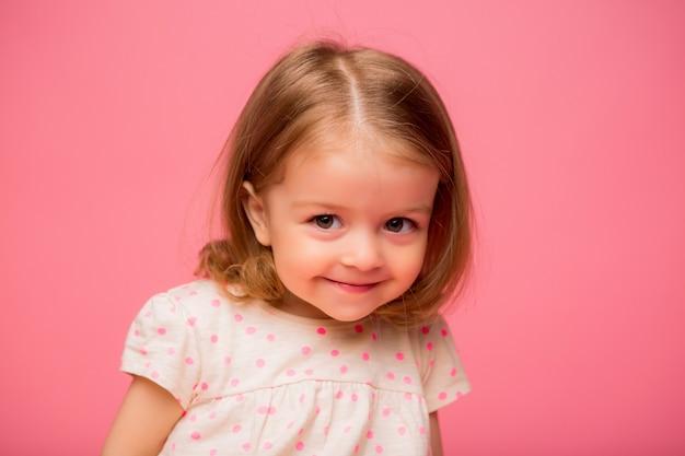 Mała dziewczynka ono uśmiecha się na różowym tle