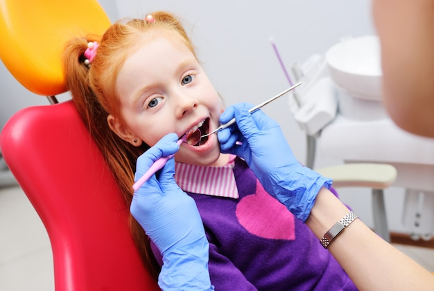 Mała dziewczynka ono uśmiecha się w czerwonym stomatologicznym krześle. dentysta bada zęby pacjenta dziecka. dentysta dziecięcy