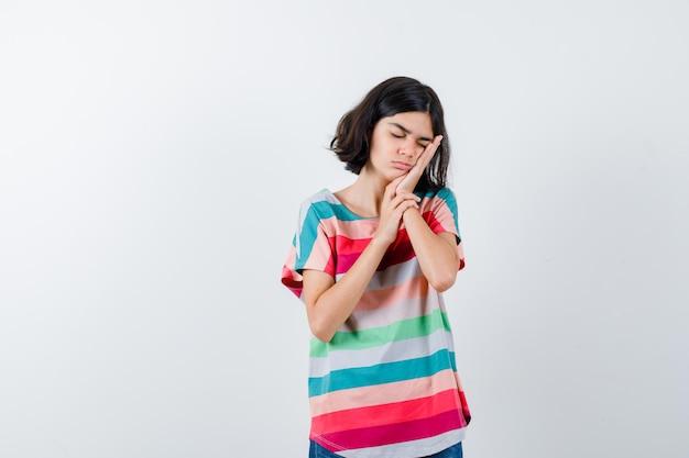 Mała dziewczynka opierając policzek na dłoni w t-shirt i patrząc śpiący. przedni widok.