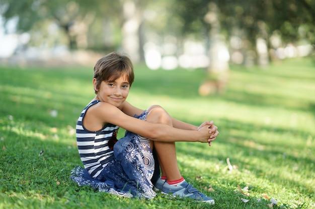 Mała dziewczynka, osiem lat, siedzi na trawie na zewnątrz.