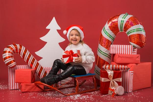 Mała dziewczynka otoczona prezentami świątecznymi i elementami
