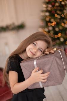 Mała dziewczynka otwiera świąteczny prezent od świętego mikołaja. świąteczna opowieść. szczęśliwe dzieciństwo.