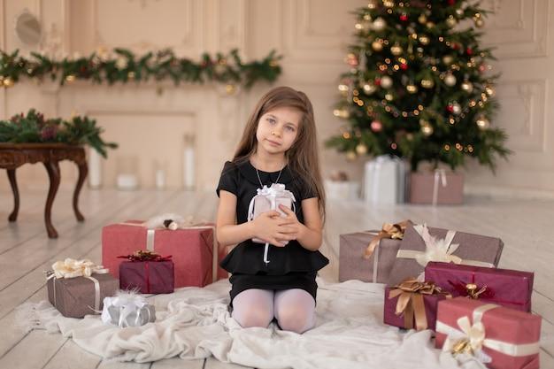 Mała dziewczynka otwiera świąteczny prezent od świętego mikołaja