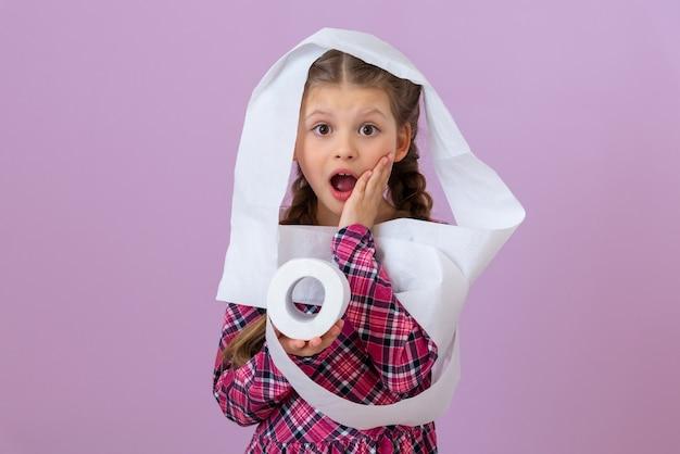 Mała dziewczynka owinięta papierem toaletowym jest zaskoczona z szeroko otwartymi ustami.