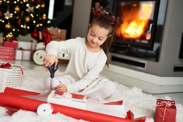 Mała dziewczynka pakuje prezenty świąteczne
