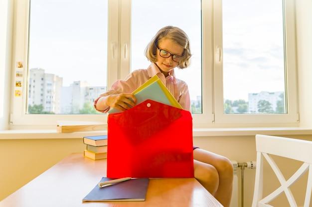 Mała dziewczynka pakuje swój szkolny plecak, siedząc na biurku. szkoła, edukacja, wiedza i dzieci.