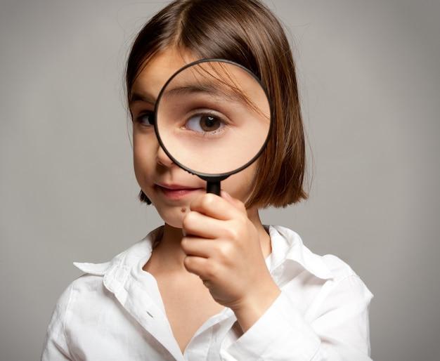 Mała dziewczynka patrząc na kamery przez szkło powiększające