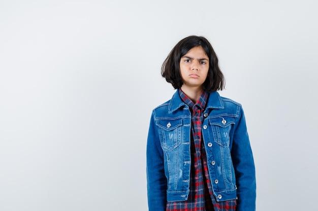 Mała dziewczynka patrząc na kamery w koszuli, kurtce i patrząc ponury, widok z przodu.