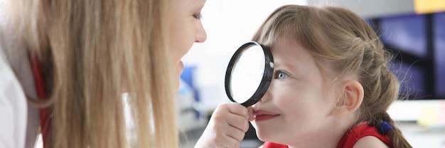 Mała dziewczynka patrząc na lekarza pediatry z lupą w klinice korekcji wzroku w