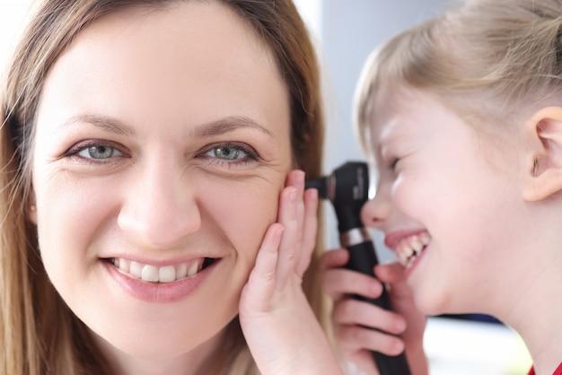Mała dziewczynka patrząc na ucho kobiety lekarz z otoskopem