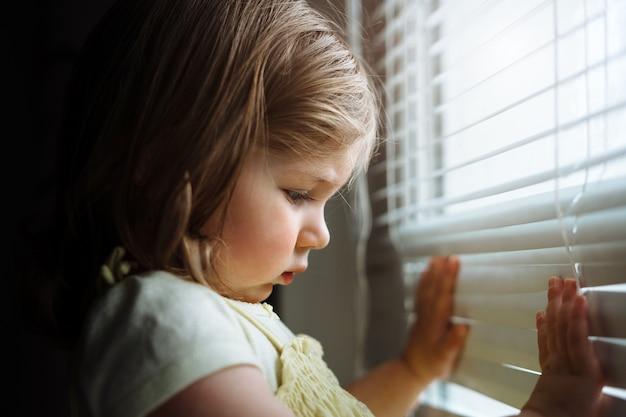 Mała dziewczynka patrząc przez okno przez żaluzje.