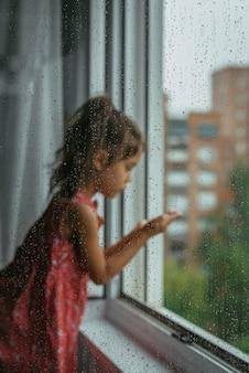 Mała dziewczynka patrząc przez okno w deszczowy dzień