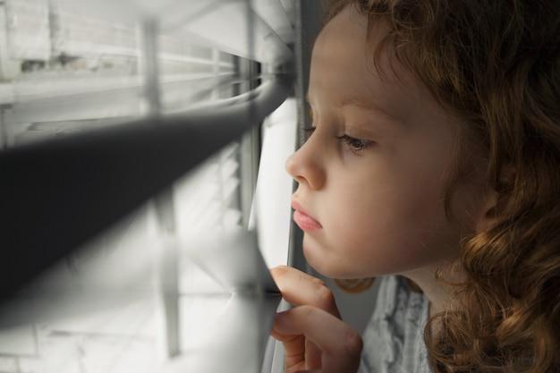 Mała dziewczynka patrząc przez okno