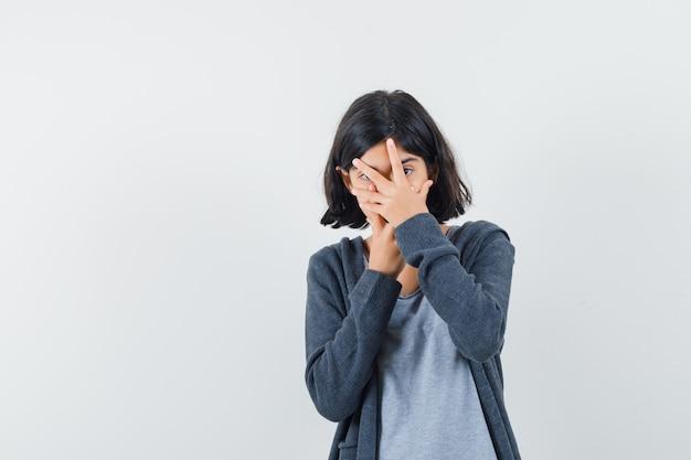 Mała dziewczynka patrząc przez palce w t-shircie, kurtce i wyglądająca zaciekawiona,