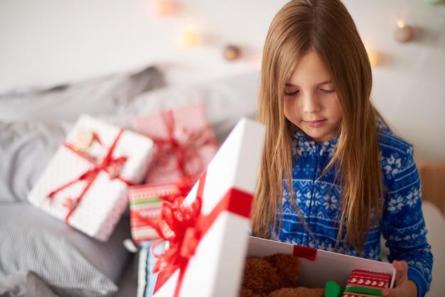 Mała dziewczynka patrząc wewnątrz prezentu bożonarodzeniowego