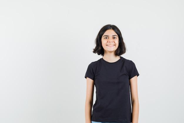 Mała dziewczynka patrząc z przodu w czarnej koszulce i wyglądająca wesoło. przedni widok.
