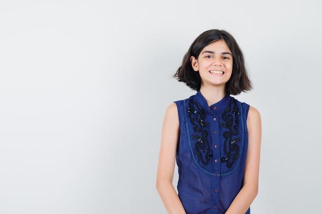 Mała dziewczynka patrząc z przodu w niebieskiej bluzce i patrząc radośnie.