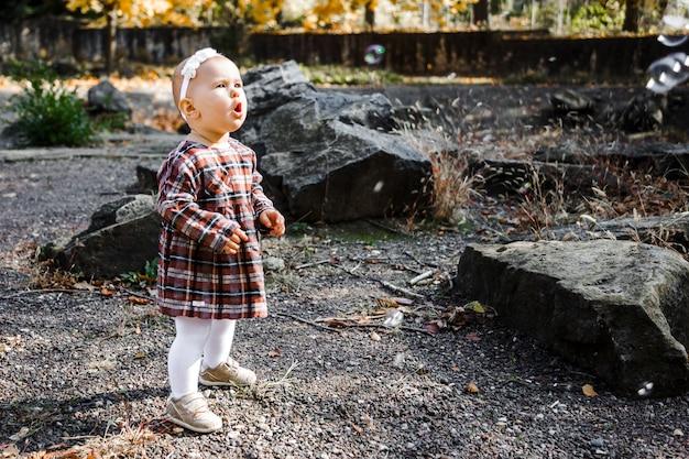 Mała dziewczynka patrzy na bańki mydlane w parku jesienią