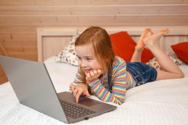 Mała dziewczynka patrzy na komputer z różnymi emocjami. dziewczyna gra na komputerze
