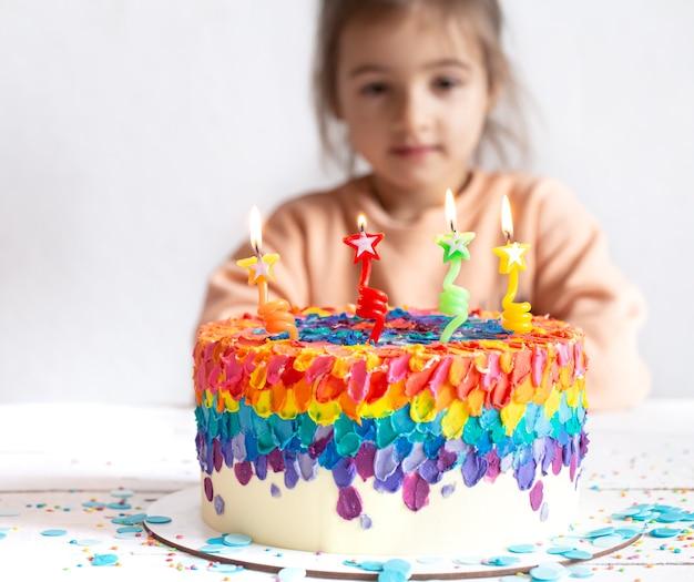 Mała dziewczynka patrzy na piękny tort urodzinowy. koncepcja niespodzianka urodzinowa.