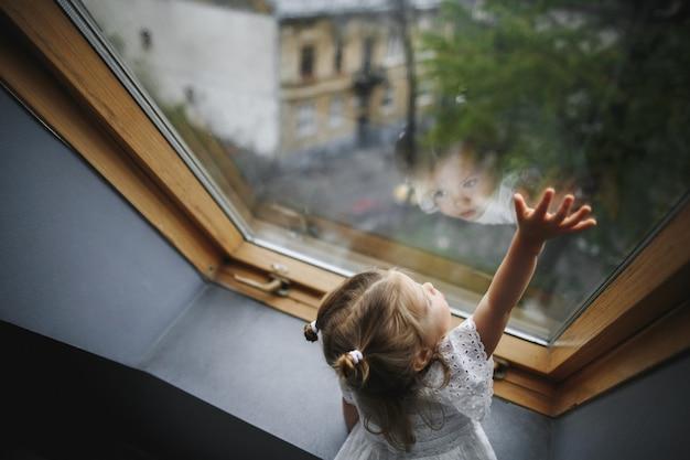 Mała dziewczynka patrzy przez okno