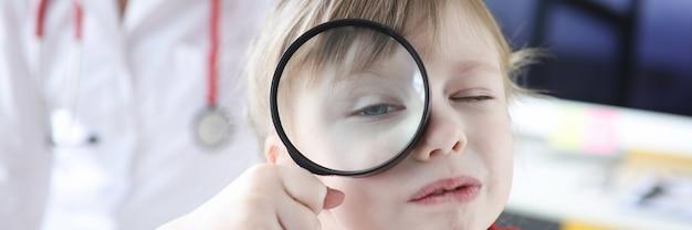 Mała dziewczynka patrzy przez szkło powiększające w tle jest lekarzem. znalezienie pediatry do koncepcji dziecka