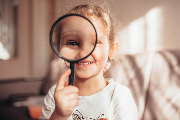 Mała dziewczynka patrzy przez szkło powiększające