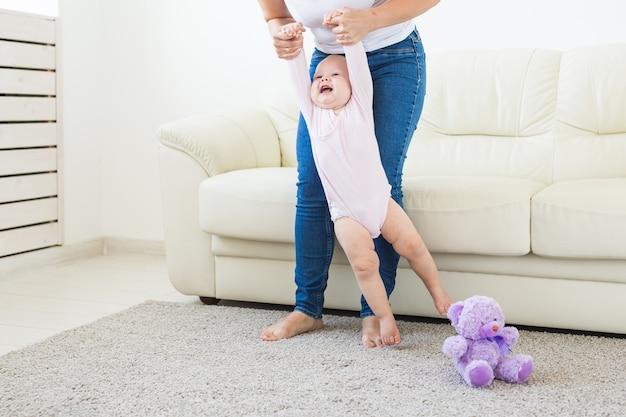 Mała dziewczynka pierwsze kroki z pomocą mamy