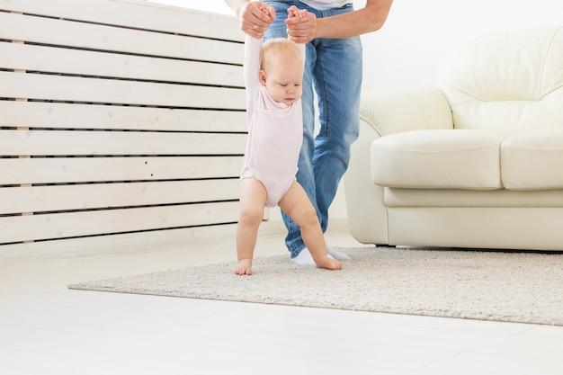 Mała dziewczynka pierwsze kroki z pomocą ojca