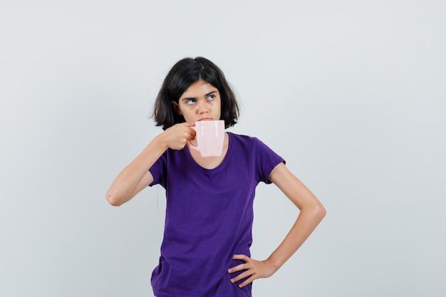 Mała dziewczynka pije herbatę w t-shirt i wygląda zamyślony.