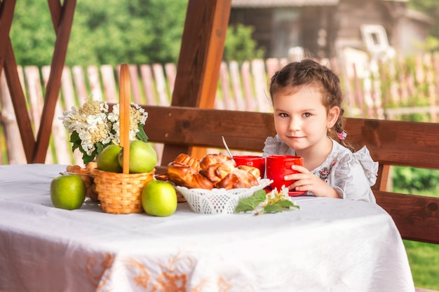 Mała dziewczynka pije herbatę z bułkami