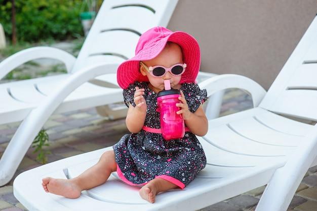 Mała dziewczynka pije z kubka w czerwonym kapeluszu