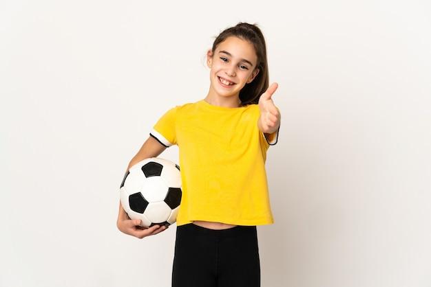 Mała dziewczynka piłkarz na białym tle, ściskając ręce, aby zamknąć dobrą ofertę