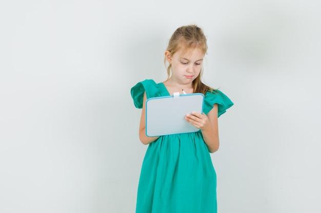 Mała dziewczynka pisze coś na pokładzie w zielonej sukni widok z przodu.