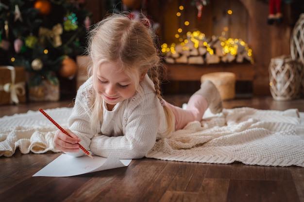 Mała dziewczynka pisze list świętego mikołaja i marzy o prezentu