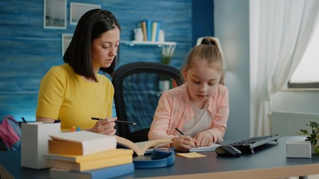Mała dziewczynka pisze na notatniku długopisem, podczas gdy matka udziela pomocy