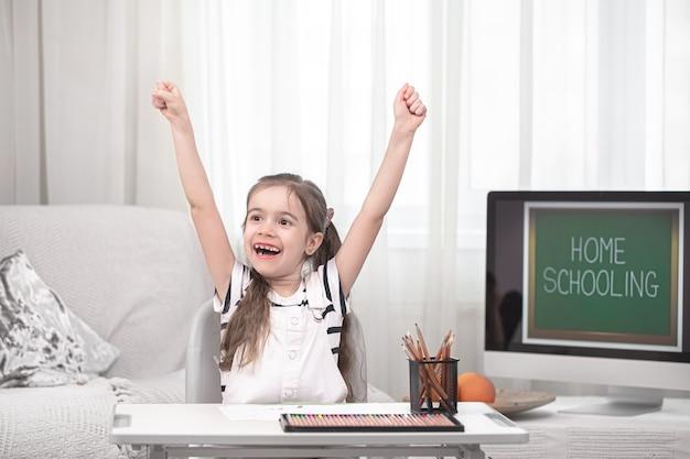 Mała dziewczynka pisze pracę domową w domu. edukacja domowa i edukacja