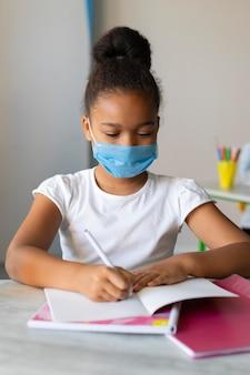 Mała dziewczynka pisze w zeszycie podczas noszenia maski medycznej