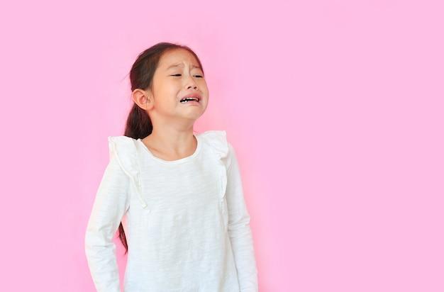 Mała dziewczynka płacz na różowym tle