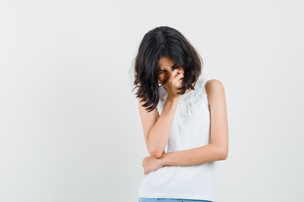 Mała dziewczynka płacze w białej bluzce, szortach i wygląda na obrażoną. przedni widok.