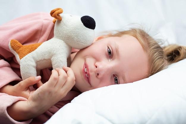 Mała dziewczynka płacze w łóżku i ściska zabawkę