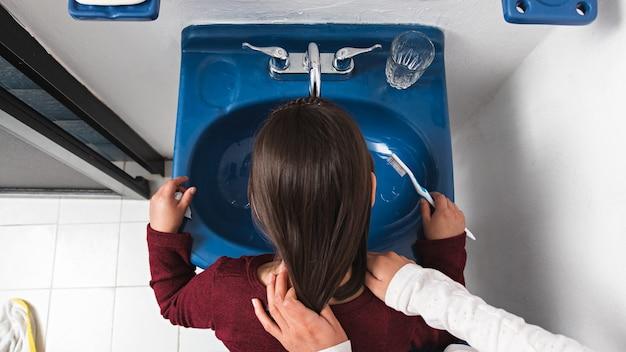 Mała dziewczynka płucze usta po umyciu zębów w łazience