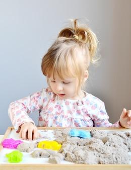 Mała dziewczynka plyaying z kinetycznym piaskiem w domu