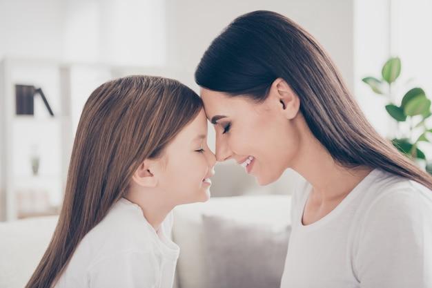 Mała dziewczynka pochyla głowę do młodej mamusi w domu w domu