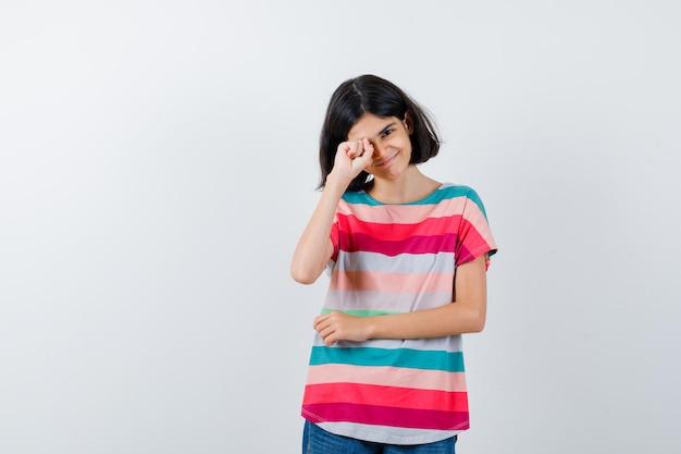 Mała dziewczynka pociera oko w t-shirt i wygląda wesoło. przedni widok.