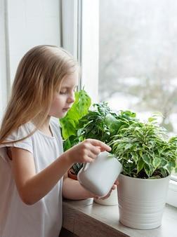 Mała dziewczynka podlewa rośliny doniczkowe w swoim domu