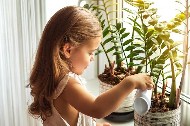 Mała dziewczynka podlewania kwiatów w domu